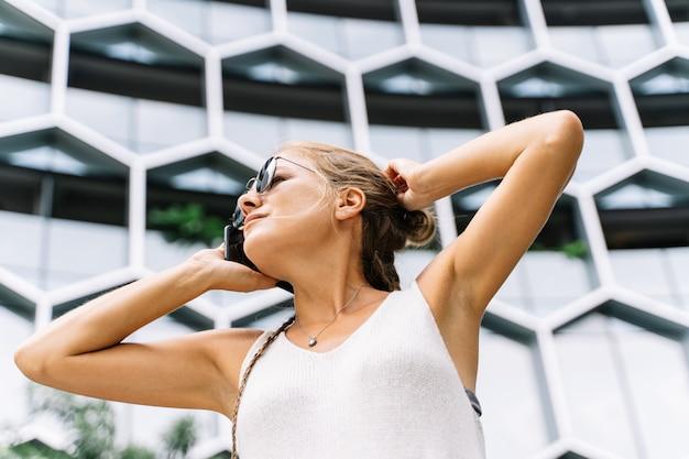 Blondynki dziewczyna opowiada przed wiszącą ozdobą z okularami przeciwsłonecznymi stoi przed nowożytnym budynkiem