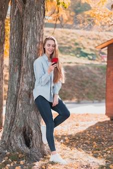 Blondynki dziewczyna patrzeje na telefonie i obsiadaniu obok drzewa