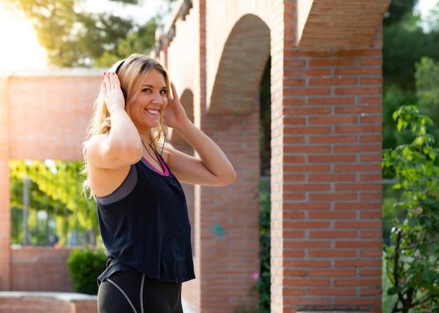 Blondynki dziewczyna słucha muzyka podczas gdy robić sportom
