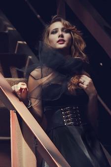 Blondynki dziewczyna w czerni sukni starej zaniechanej fabryce