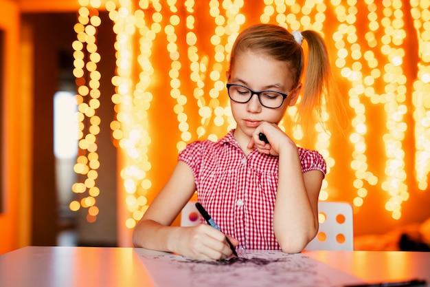 Blondynki dziewczyna w dużych czarnych szkłach rysuje santa claus. boże narodzenie i nowy rok, żółty bokeh
