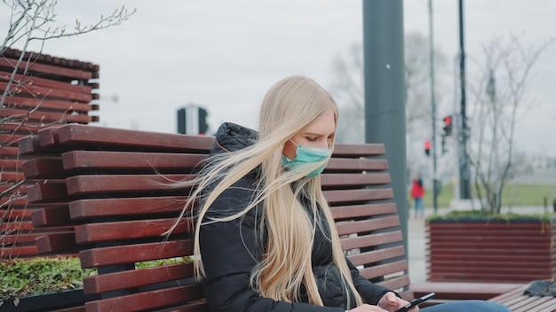 Blondynki dziewczyna w medycznym maskowym obsiadaniu na ławce i używać telefonie