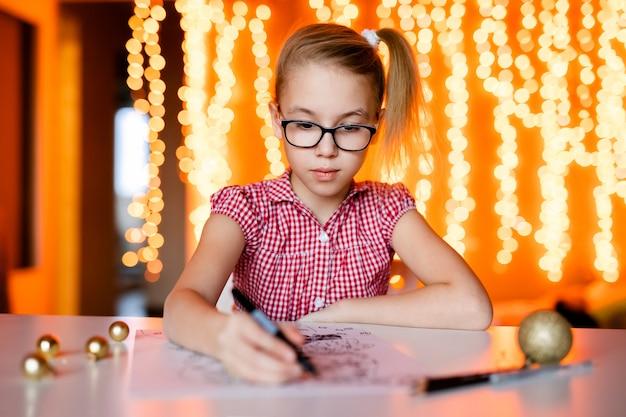 Blondynki dziewczyna w różowej sukni i dużych czarnych szkłach rysuje santa claus. motyw świąteczny