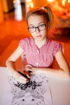 Blondynki dziewczyna w różowej sukni i dużych czarnych szkłach rysuje santa claus