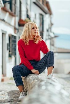 Blondynki dziewczyna z czerwoną koszula cieszy się życie outdoors.