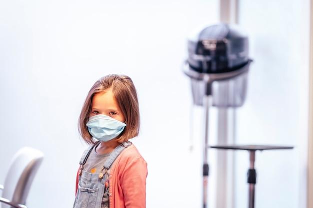 Blondynki dziewczyna z maską po fryzury u fryzjera. ponowne otwarcie ze środkami bezpieczeństwa dla fryzjerów w pandemii covid-19