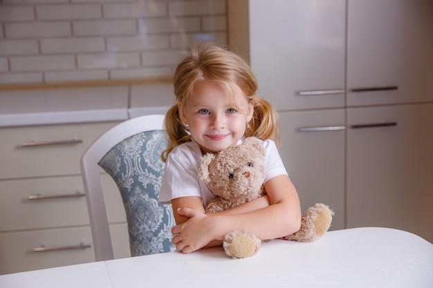 Blondynki dziewczynka z niedźwiedź zabawką w kuchni przed pora snu