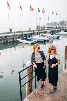 Blondynki dziewczyny w okularach przeciwsłonecznych chodzą na molu na tle jeziornego gardzie, włochy