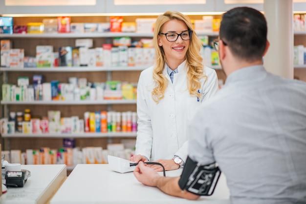 Blondynki farmaceuta mierzy ciśnienie krwi młody męski pacjent.