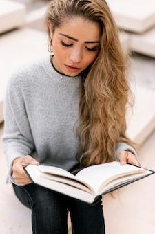 Blondynki kobieta czyta jej książkę