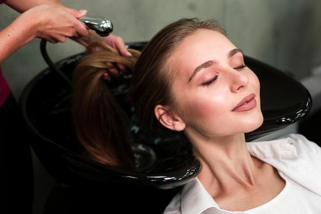 Blondynki kobieta dostaje włosy myjącego przy salonem