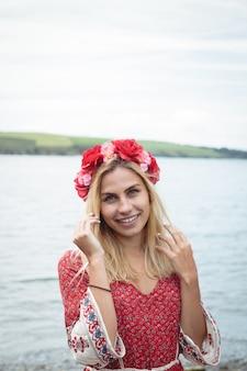 Blondynki kobieta jest ubranym kwiat tiary pozycję blisko rzeki