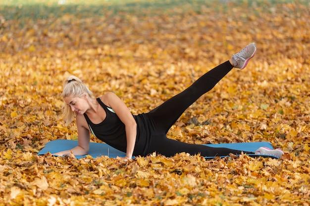 Blondynki kobieta kłaść na joga dywaniku w naturze