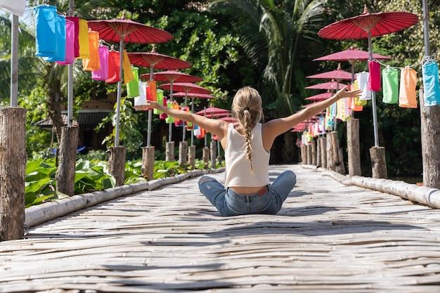 Blondynki kobieta na jej plecach siedzi po środku drewnianego mosta z rękami w powietrzu