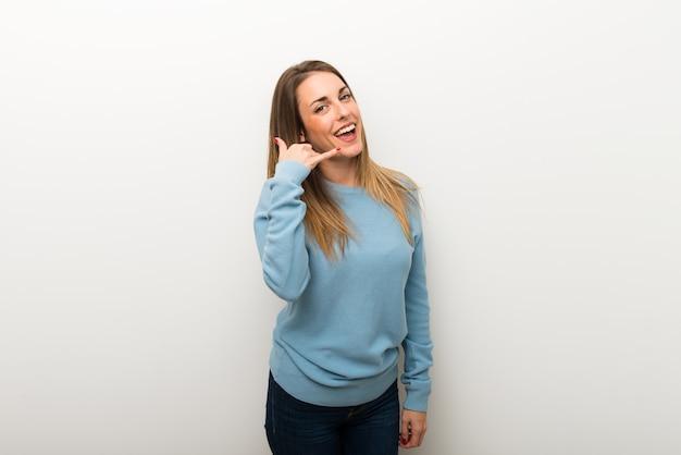 Blondynki kobieta na odosobnionej biel ścianie robi telefonu gestowi. zadzwoń do mnie znak