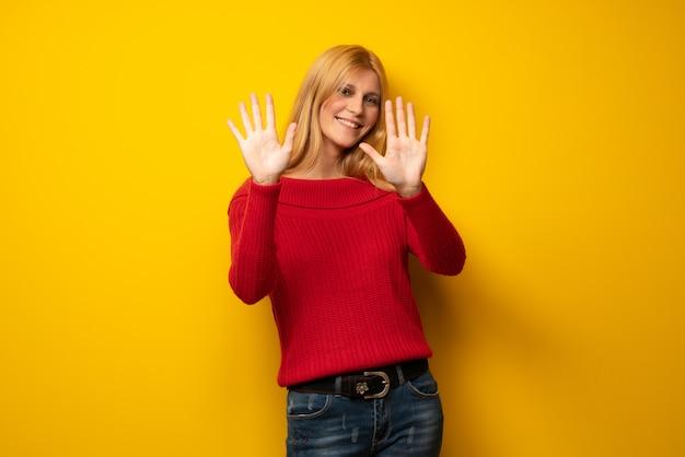 Blondynki kobieta nad żółtą ścianą liczy dziesięć z palcami