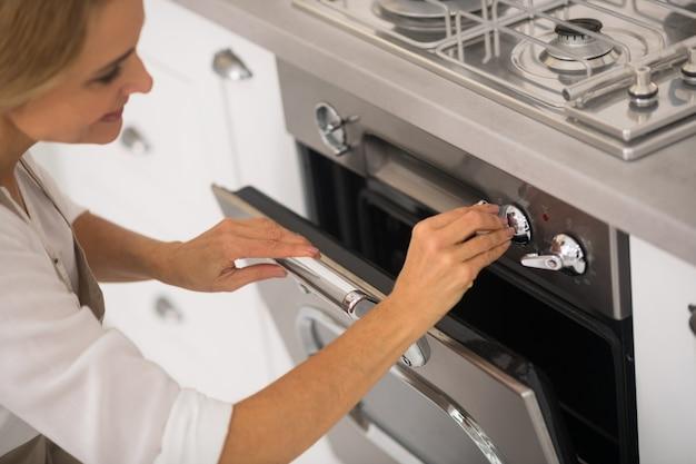 Blondynki kobieta otwierająca piekarnik w kuchni