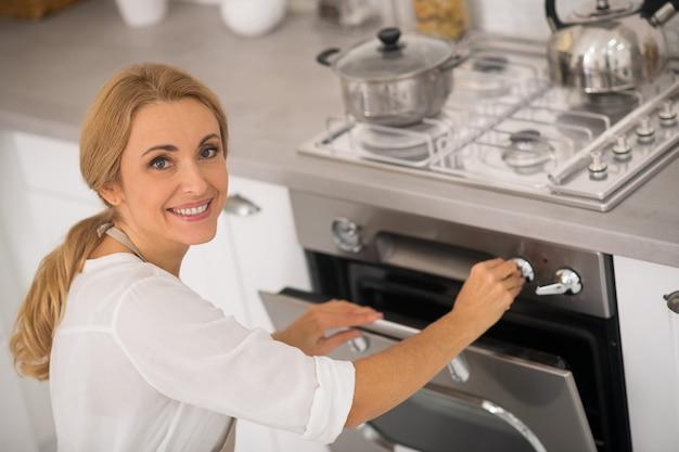 Blondynki Kobieta Otwierająca Piekarnik W Kuchni Premium Zdjęcia