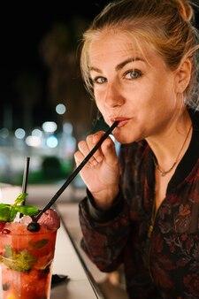 Blondynki kobieta patrzeje czerwonego koktajl z słomą na tarasie przy nocą i pije