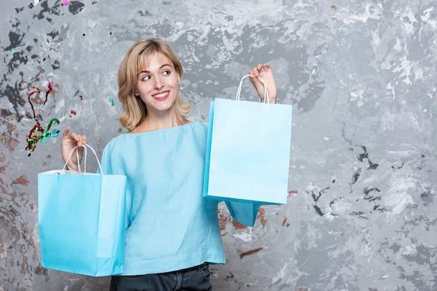 Blondynki kobieta patrzeje papierowe torby