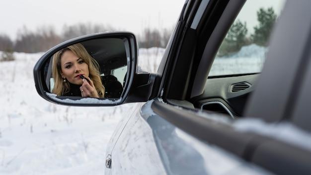Blondynki kobieta patrzeje w samochodowym lusterka wstecznego i maluje wargi.
