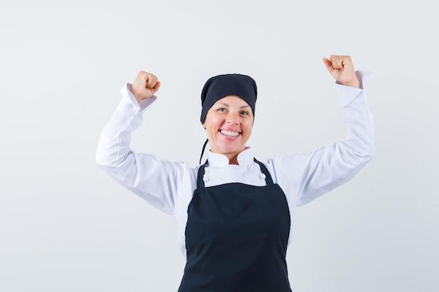 Blondynki kobieta pokazuje gest zwycięzcy w czarnym mundurze kucharza i wygląda na szczęśliwego.