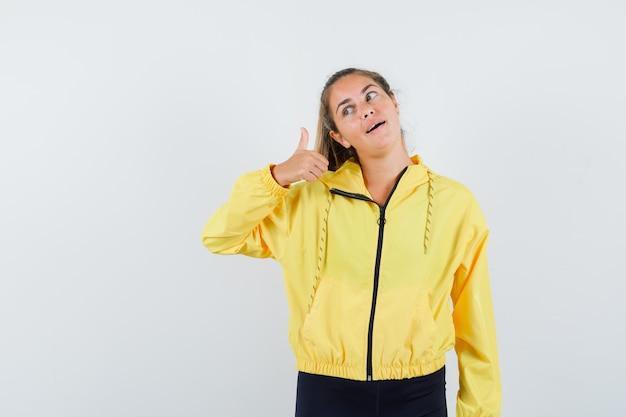 Blondynki kobieta pokazuje kciuk w żółtej bomberce i czarnych spodniach i wygląda na szczęśliwego