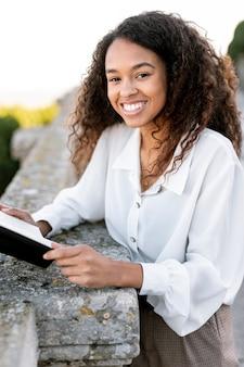 Blondynki kobieta pozuje outdoors podczas gdy trzymający książkę