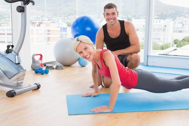 Blondynki kobieta pracuje na ćwiczenie macie z jej trenerem
