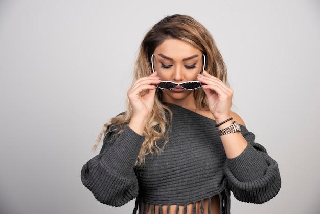 Blondynki kobieta próbuje okularów w przypadkowym stroju.