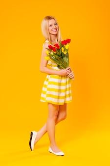Blondynki kobieta trzyma bukiet wiosennych kwiatów