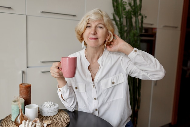 Blondynki kobieta trzyma filiżankę herbata i siedzi przy nowożytną kuchnią