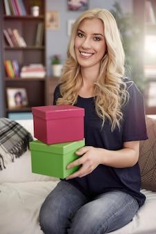 Blondynki kobieta trzyma kolorowe pudełka