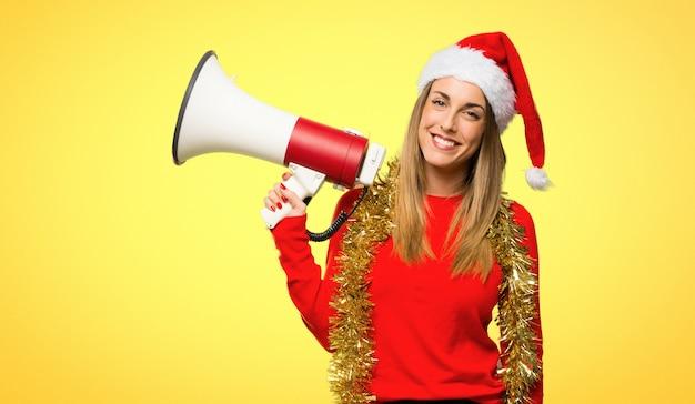 Blondynki kobieta ubierał up dla boże narodzenie wakacji krzyczy przez megafonu ogłaszać w ten sposób
