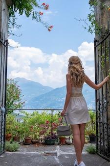 Blondynki kobieta w biel sukni przy como jeziorem