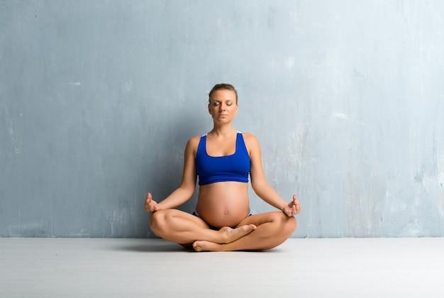 Blondynki kobieta w ciąży robi joga