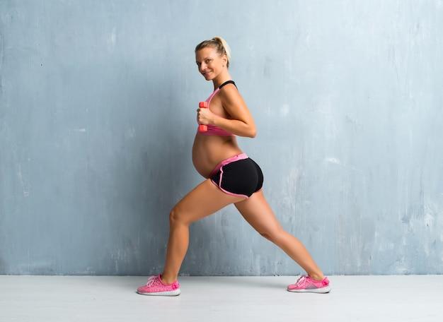 Blondynki kobieta w ciąży robi sportowi robi weightlifting