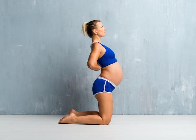 Blondynki kobieta w ciąży robi sportowi