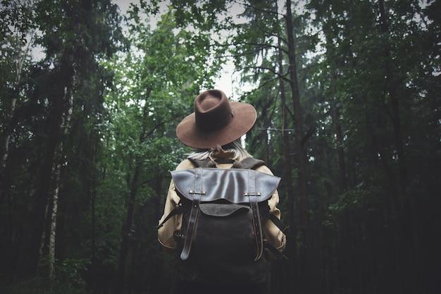 Blondynki kobieta w kapeluszu z plecakiem w deszczowym dniu w lesie