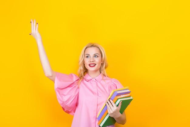 Blondynki kobieta w różowej bluzce z stosem książki