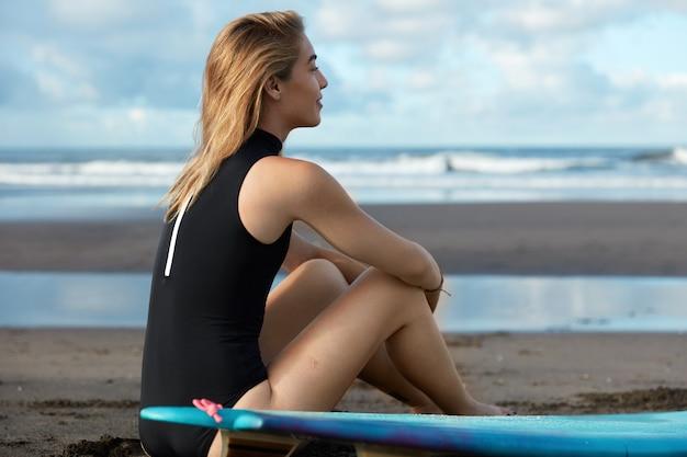 Blondynki kobieta w stroju kąpielowym z deską surfingową na plaży
