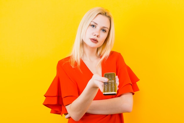 Blondynki kobieta w sukni z pilot do tv