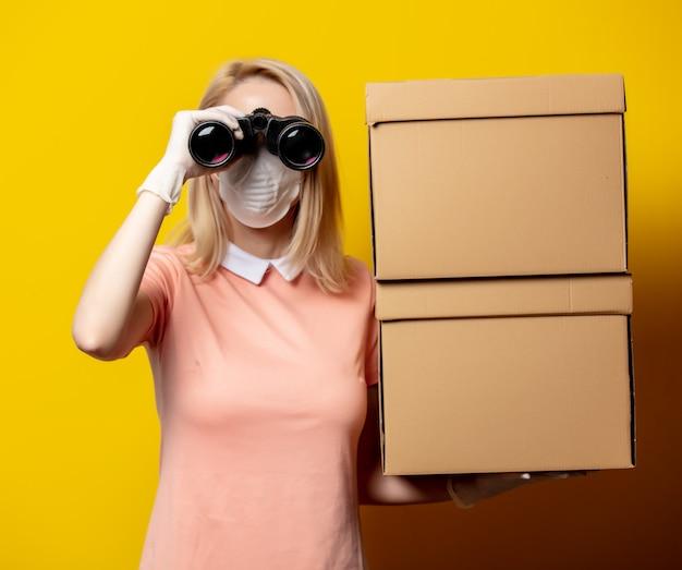 Blondynki kobieta w twarzy masce z doręczeniowymi pudełkami i lornetkami na kolor żółty ścianie