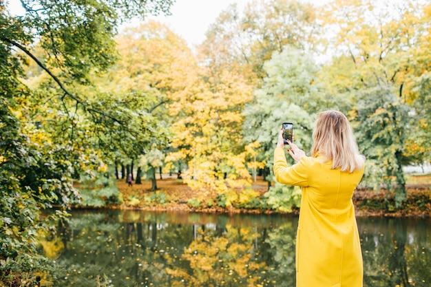 Blondynki kobieta w żółtym żakiecie robi fotografii z telefonem komórkowym w parku