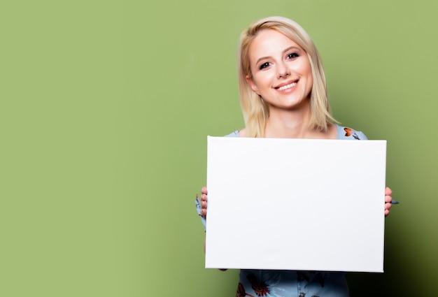 Blondynki kobieta z białym sztandarem na zieleni ścianie