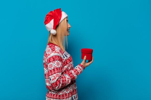 Blondynki kobieta z czapką mikołaja w widoku profilu, która chce skopiować przestrzeń do przodu, myśleć, wyobrażać sobie lub marzyć