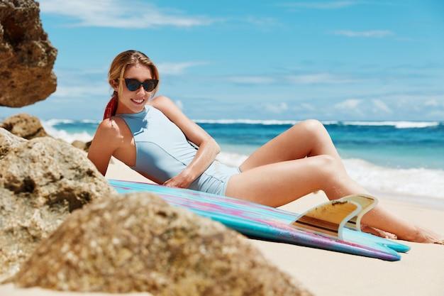 Blondynki kobieta z deską surfingową na plaży