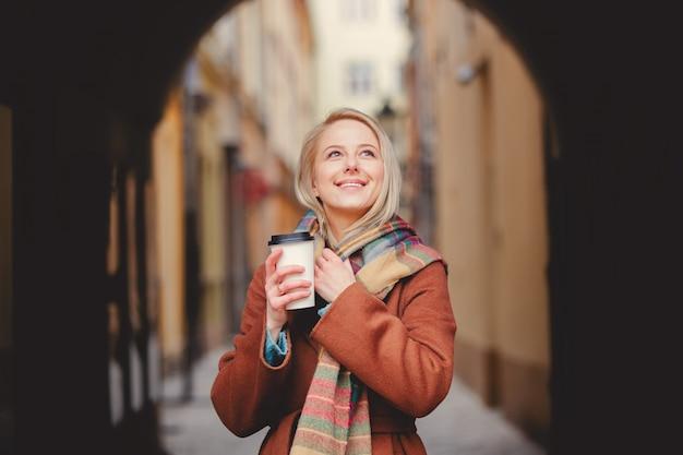 Blondynki kobieta z filiżanką kawy w starym miasteczku