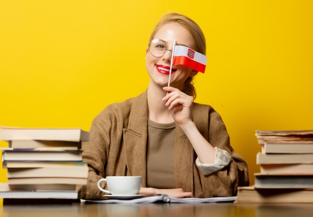 Blondynki kobieta z flaga polska i książkami na kolorze żółtym