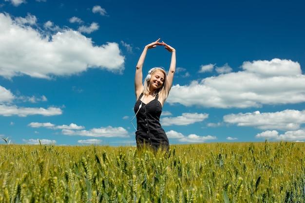 Blondynki kobieta z hełmofonami w pszenicznym polu w słonecznym dniu